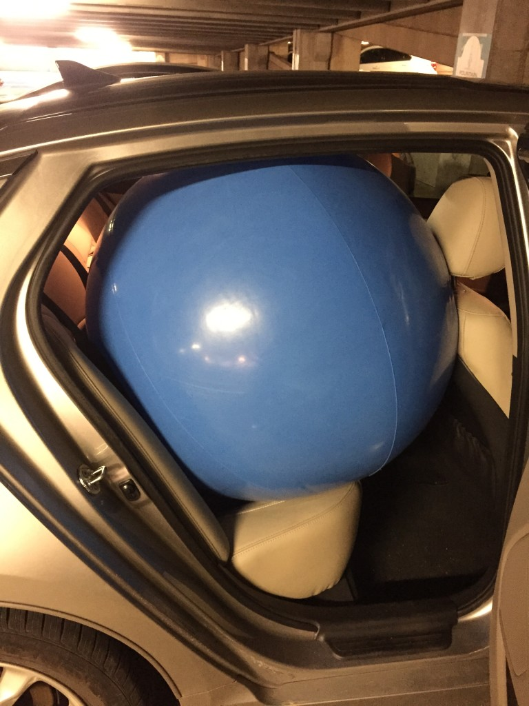 giant blue beach ball squeezed into backseat of car