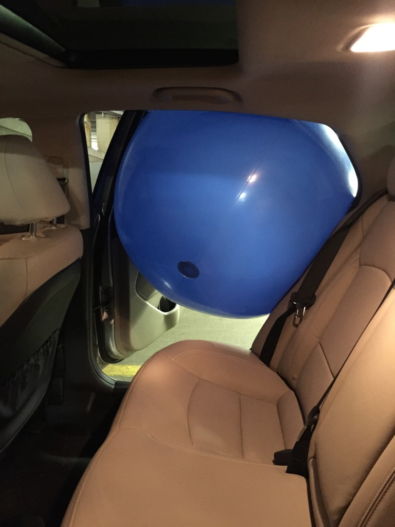 giant blue beach ball stuck in door of car