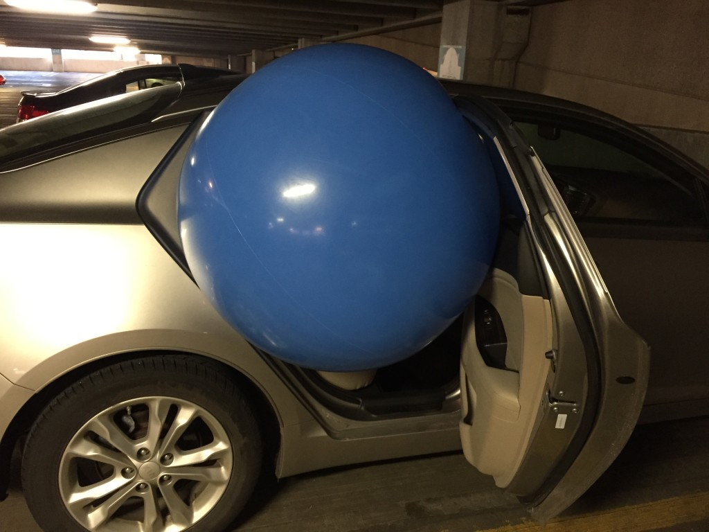 giant blue beach ball being stuffed into backseat of car