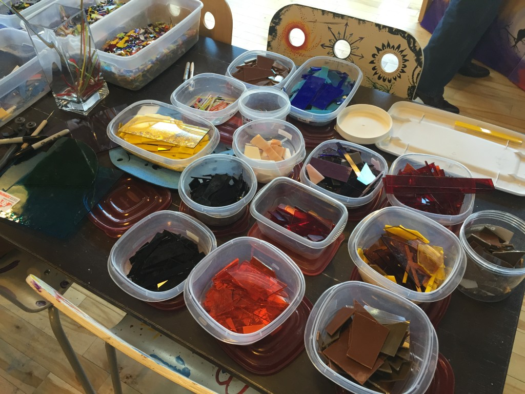 pieces of colored glass sorted into plastic tubs