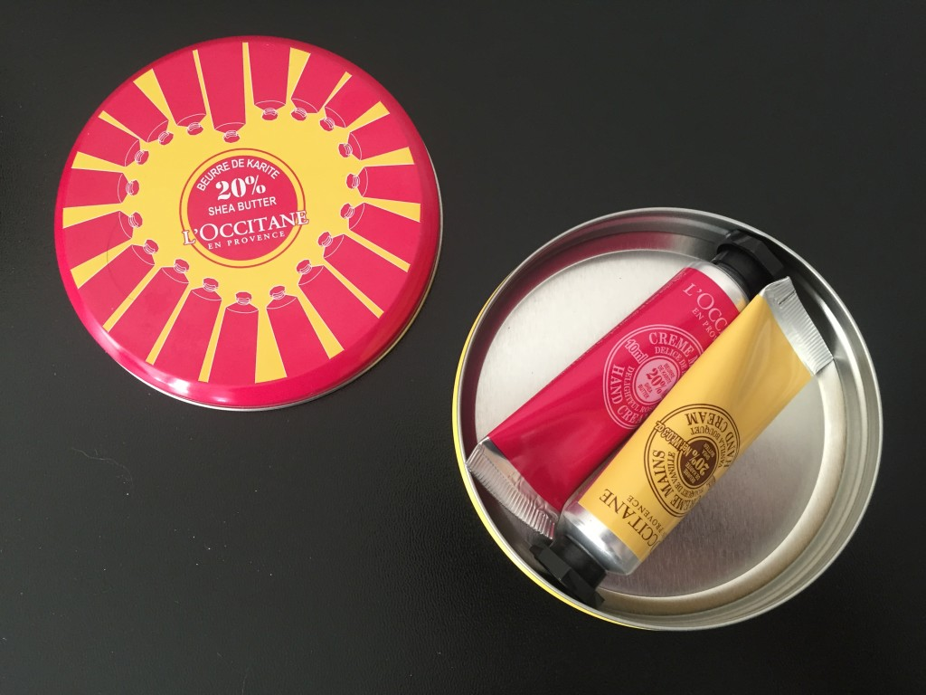 inside of l'occitane collector's tin with two mini hand creams
