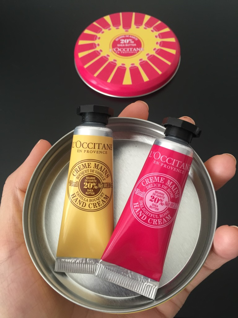 size comparison of l'occitane collector's tin and mini hand creams against person's hand