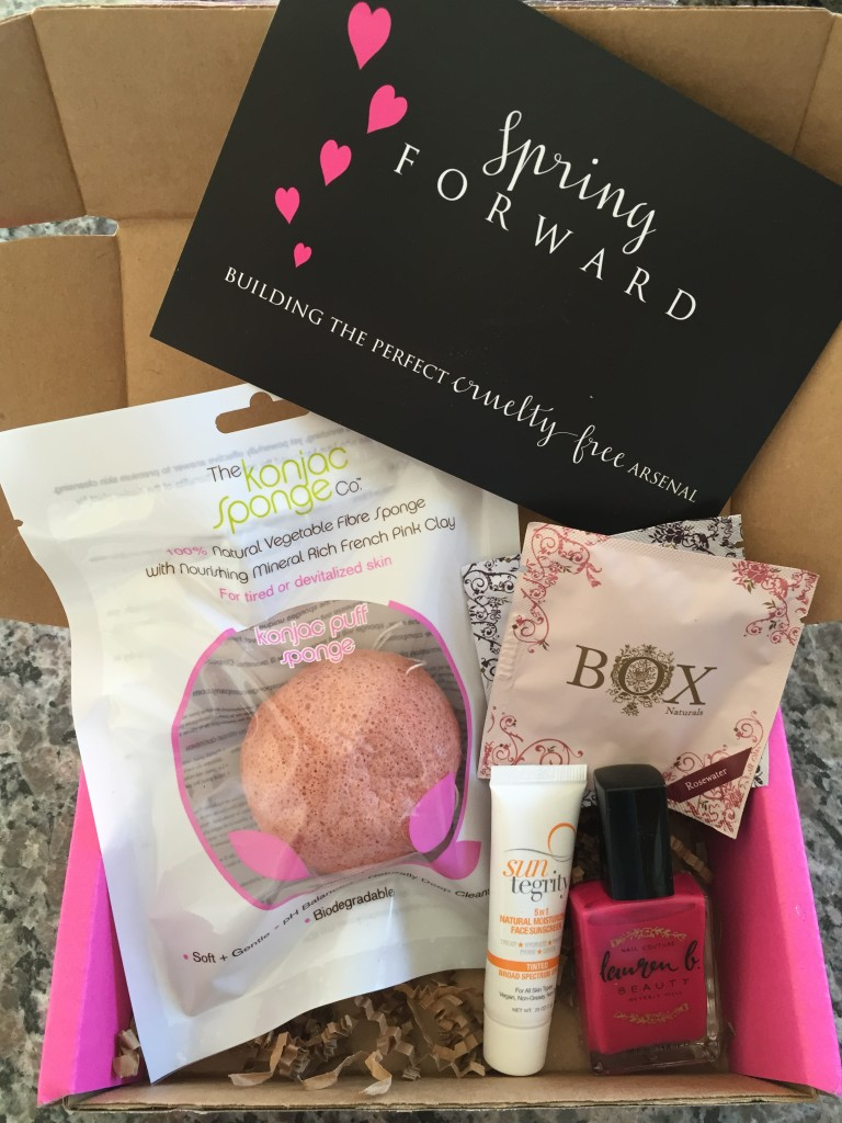 contents of petit vour april 2015 box with the konjac sponge co puff, box naturals luxe towelettes, suntegrity tinted face sunscreen, lauren b nail polish, and info card with spring forward theme