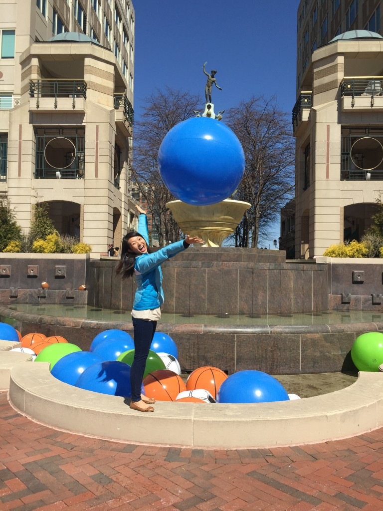excited girl throwing beach ball in air by fountain filled with balls