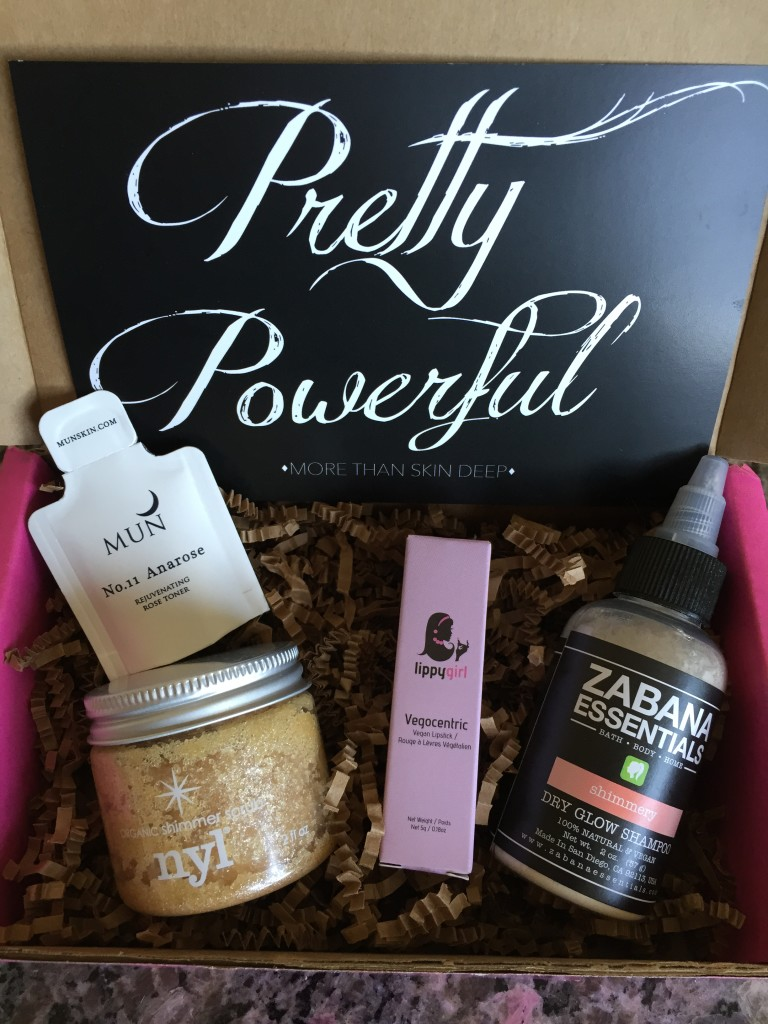 contents of petit vour may 2015 box with mun anarose toner, nyl organic shimmer scrub, lippygirl vegan lipstick, zabana essentials dry shampoo, and info card with pretty powerful theme