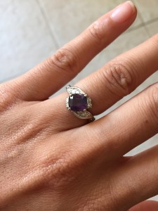 purple sapphire engagement ring on hand