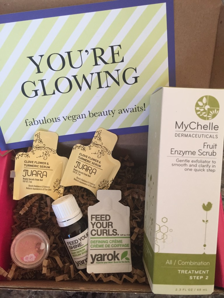 contents of petit vour august 2015 box with juara serum, modern minerals finishing glow, yarok serum and defining creme, mychelle enzyme scrub, and info card with you're glowing theme