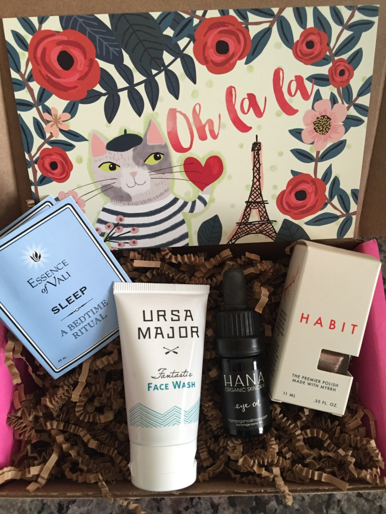 contents of petit vour october 2015 box with essence of vali essential oil, ursa major face wash, hana eye oil, habit nail polish, and info card with oh la la theme