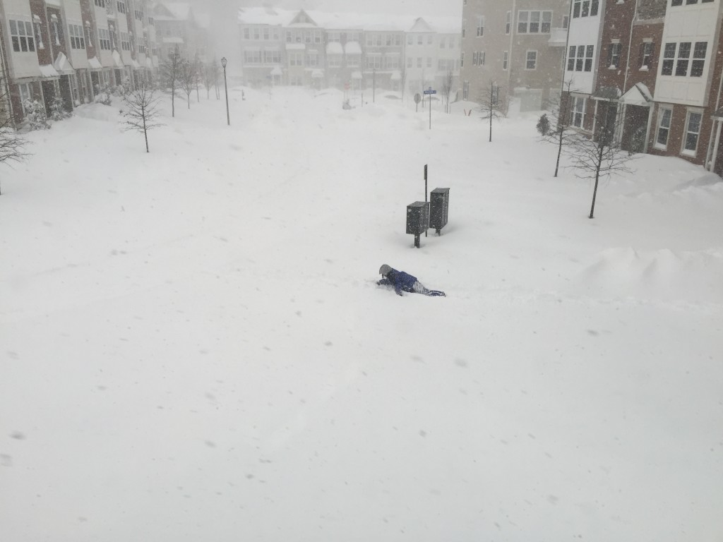 man crawling on belly in deep snow during blizzard 2016
