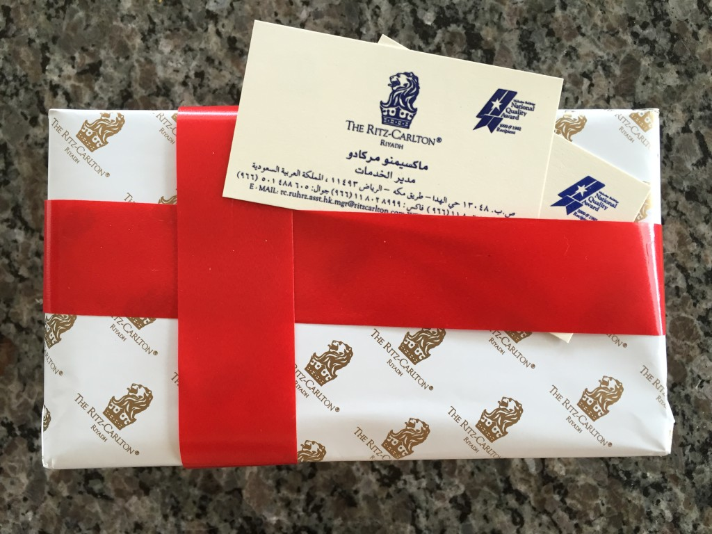 ritz-carlton gift box with white wrapping paper and red ribbon