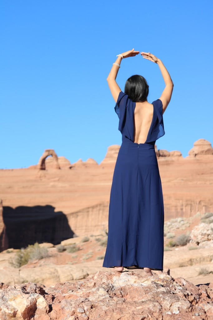 standing with arms overhead with delicate arch in the background