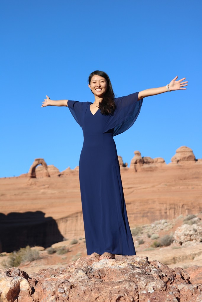 standing with arms outstretched with delicate arch in the background