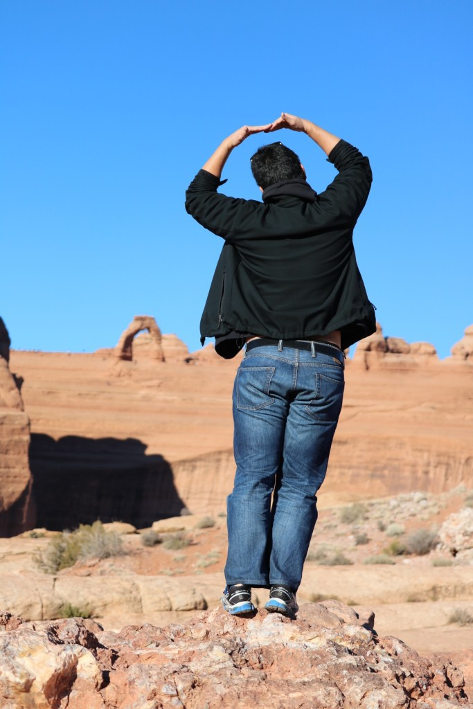 standing with arms outstretched overhead with delicate arch in the background