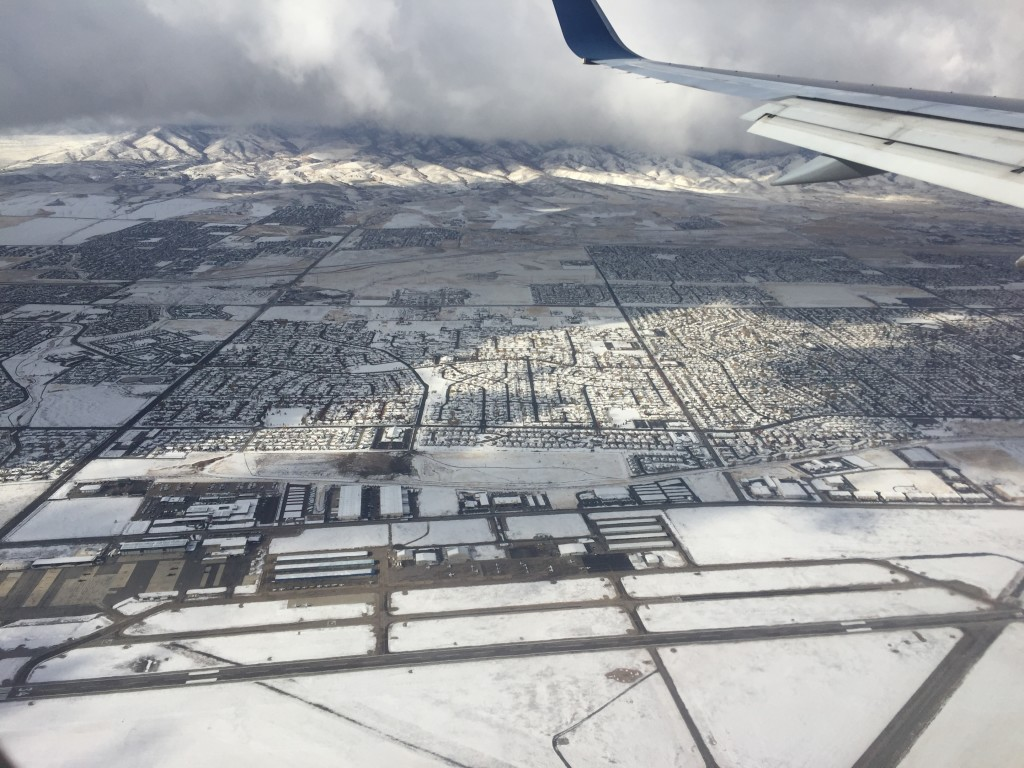view of snow covering salt lake city from airplane landing