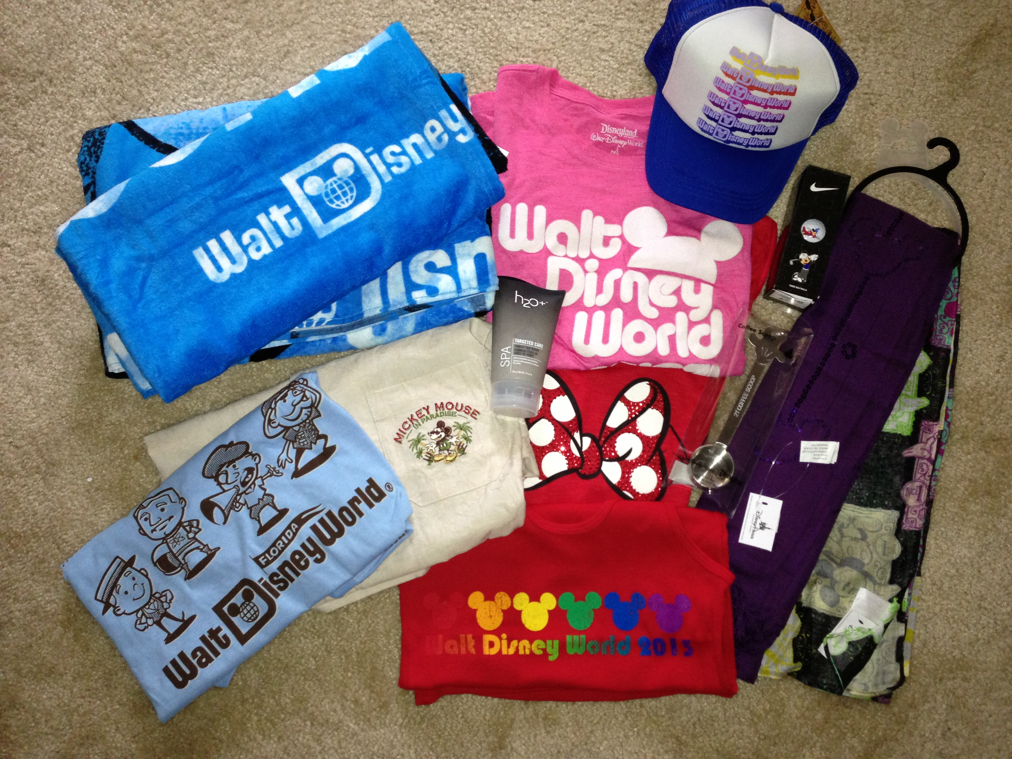 Disney Products Laid Out Including Beach Towels Tshirts Trucker Hat Tank Tops
